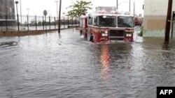 Một chiếc xe chữa lửa chạy trên đường phố bị ngập lụt ở Brooklyn, New York, ngày 28/8/2011