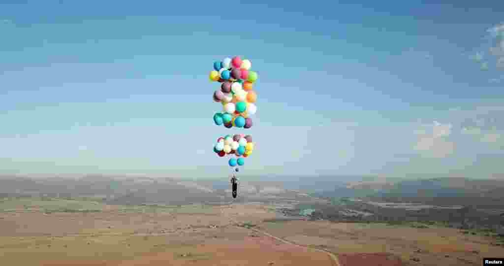 Tom Morgan, from Bristol-based company The Adventurists, flies in a chair tied to large party balloons near Johannesburg, South Africa.