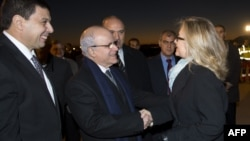 Jazoir Tashqi ishlar vaziri Murod Medelchi (chapda) AQSh Davlat kotibi Xillari Klintonni olqishlamoqda, 29-oktabr, 2012-yil.