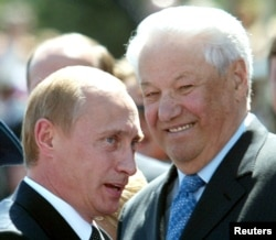 FILE - Russian President Vladimir Putin speaks as former Russian president Boris Yeltsin, right, smiles in Red Square in Moscow, June 12, 2004.