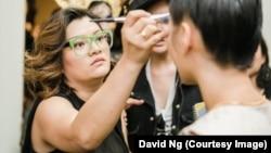 Thai designer Thunyatorn Ng applies make-up to a model.