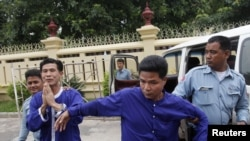 Born Samnang (2nd L) and Sok Sam Oeun (2nd R) are escorted by police officers at the Supreme Court in central Phnom Penh, Sept. 25, 2013.