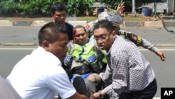 مردم در حال حمل یک پلیس مجروح در جاکارتا در روز پنجشنبه