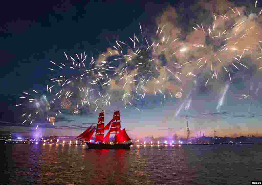 Fireworks explode over Sweden's brig Tre Kronor with scarlet sails which floats on the Neva River during the Scarlet Sails festivities marking school graduation, in St. Petersburg, Russia, June 24, 2017.