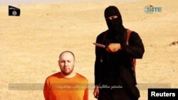 Jihadi John ដែលមានឈ្មោះពិតប្រាកដថា Mohammed Emwazi ឈរនៅក្បែរបុរសម្នាក់ដែលគេគិតថាជា Steven Sotloff នៅក្នុងវីដេអូមួយកាលពីថ្ងៃទី២៦ ខែកុម្ភៈ ឆ្នាំ២០១៥។