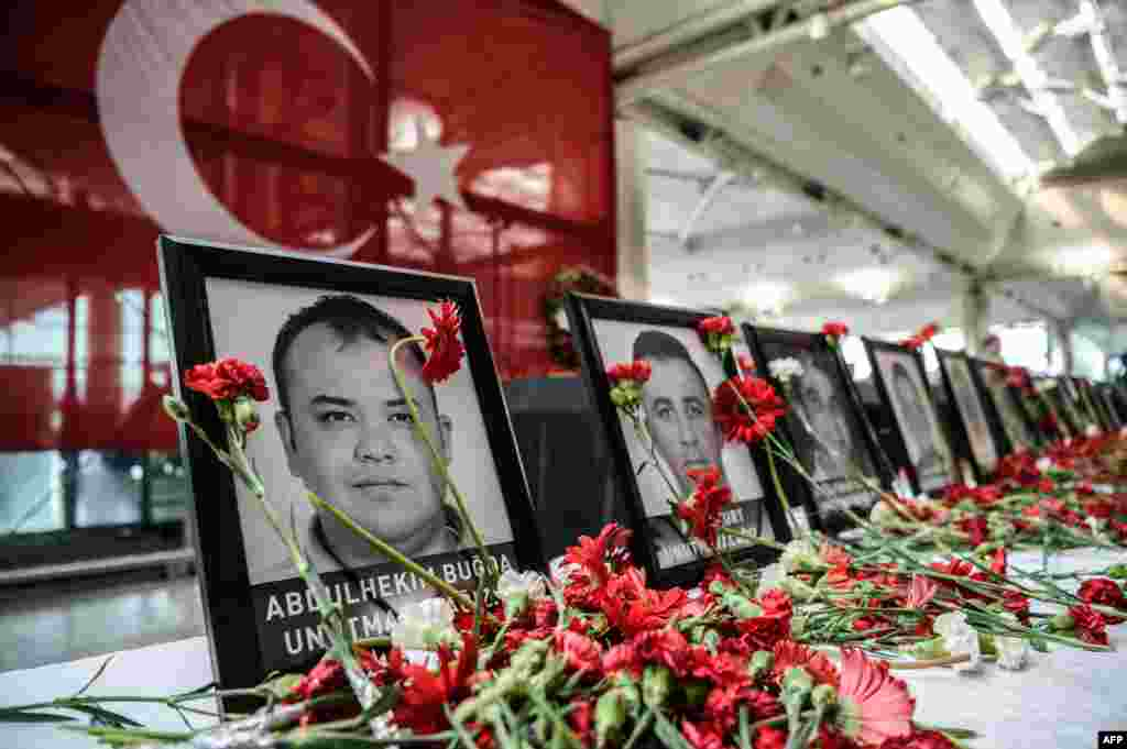 Flowers are seen by the pictures of airport employees killed by the triple suicide bombing and gun attack at Istanbul's Ataturk airport international terminal, Turkey. The death toll from the June 28 attack has risen to 43 including 19 foreigners.