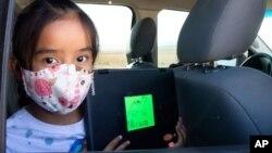 Second-grader Winona Begaye uploads homework in her family's vehicle in a dirt lot near Blue Gap, Ariz., on Sept. 25, 2020. (Megan Marples/Cronkite News via AP)
