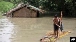 FILE - Flood-affected boys move on a banana raft near partially submerged houses in Morigaon district east of Gauhati, Assam, India, Aug. 15, 2017.