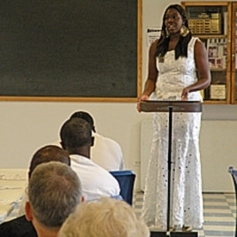 Scholarship winner Tomi Dare speaks to inmates.