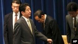 日本首相安倍晋三离开在东京举行的记者会。(2013年12月9日)