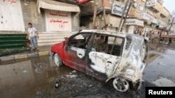 FILE - A man stands by a car damaged by a strike near al-Thawra Hospital in Hodeidah, Yemen, Aug. 2, 2018.