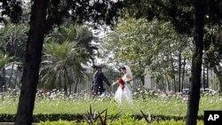 越南一对新婚夫妇在河内统一公园里合影(2008年资料照)