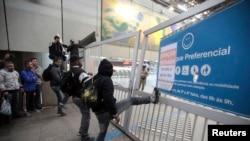 5일 브라질 상파울로에서 지하철로 출퇴근하는 시민들이 폐쇄된 지하 입구를 발로 차고 있다.