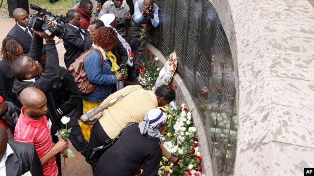 People lay flowers at the U.S. Embassy bombing memorial site in Nairobi, Kenya, Aug. 7, 2013, to mark the 15-year anniversary of the 1998 embassy bombing which killed more than 200 people and injured thousands more.