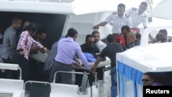 FILE - Officials carry an injured woman off the speed boat of Maldives' President Abdulla Yameen Abdul Gayoom after an explosion onboard, in Male, Sept. 28, 2015.