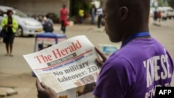 Un Zimbabwéen lit la Une du journal The Herald sur la crise au Zimbabwe, le 15 novembre 2017. AFP PHOTO /
