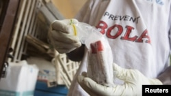 FILE - Blood samples from patients suspected of having the Ebola virus are prepared for transportation to Freetown for testing, at the Port Loko District Hospital, Sept. 27, 2014.