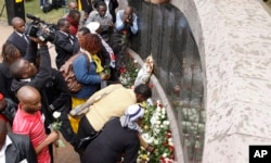 FILE - People lay flowers at the U.S. Embassy bombing memorial site in Nairobi, Kenya, Aug. 7, 2013, to mark the 15-year anniversary of the 1998 embassy bombing.