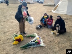 An opponent of the Dakota Access oil pipeline passes out flowers at the main protest camp near Cannon Ball, N.D., Nov. 15, 2016.