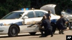 In this image made from video and released by WRCB-TV, authorities work an active shooting scene on Amincola highway near the Naval Reserve Center in Chattanooga, Tennessee, July 16, 2015.