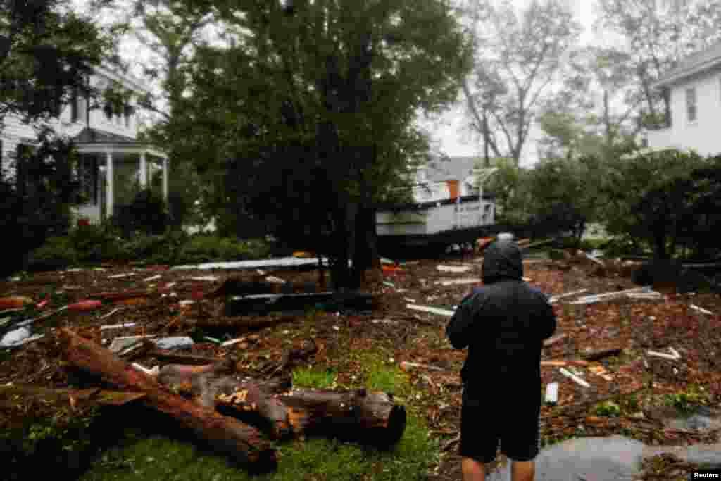 مردی در شهر «نیو برن» در کارولینای شمالی به تخریب توفان در حیاط خانه اش می نگرد.