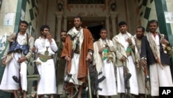 Armed tribesmen loyal to tribal leader Sheikh Sadiq al-Ahmar stand at the entrance of a building near al-Ahmar's house during clashes in Sana'a, May 26, 2011
