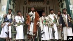 Armed tribesmen loyal to tribal leader Sheikh Sadiq al-Ahmar stand at the entrance of a building near al-Ahmar's house during clashes in Sana'a, May 26, 2011