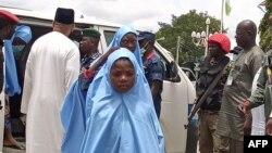 Des écolières kidnappées dans un séminaire islamique quittent une camionnette pour retrouver leurs parents à Minna, le 27 août 2021, après leur libération.