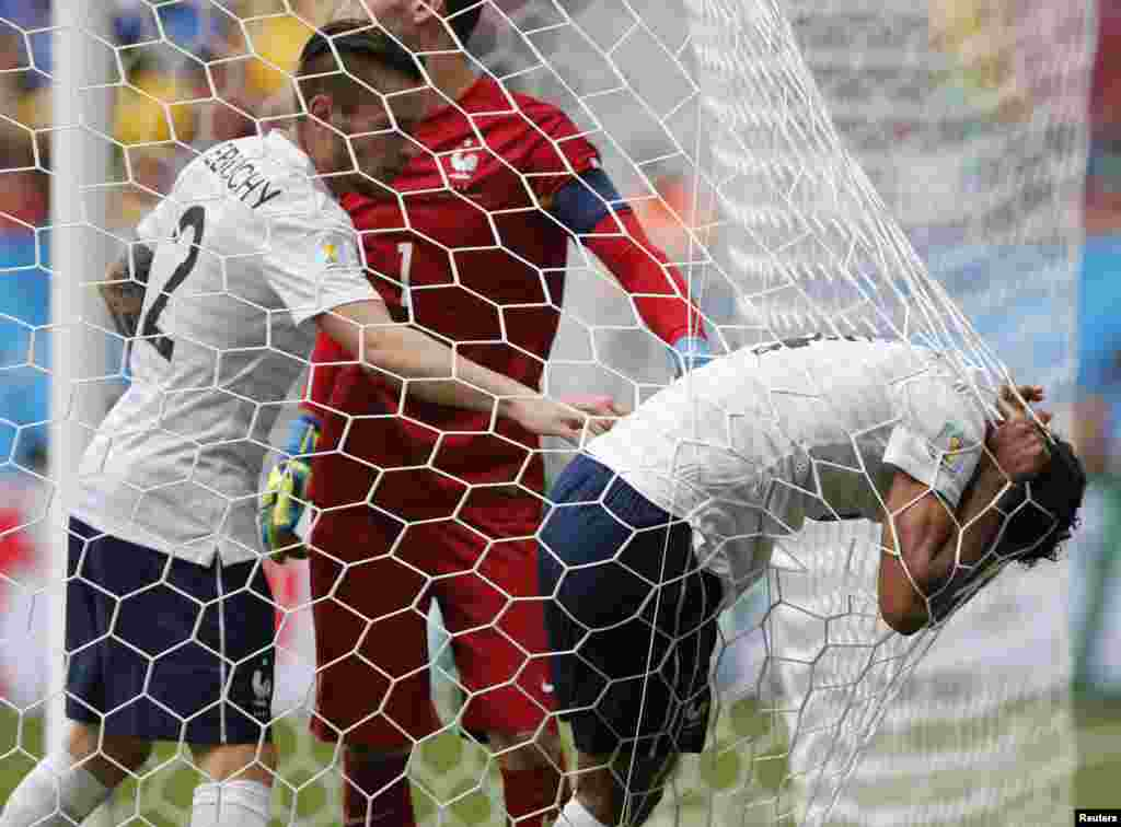 French player Raphael Varane rests on the net after an injury during the match against Nigeria, at the national stadium in Brasilia, June 30, 2014.