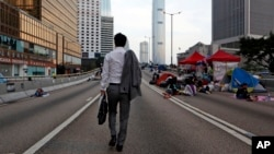 A man walks to work as the pro-democracy student protesters sleep on a roadside in the occupied areas surrounding the government complex in Hong Kong, Oct. 6, 2014. (AP Photo/Kin Cheung)