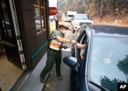 Park Ranger Anne Simmons passes maps out and directs visitors at the Hwy 140 gate as Yosemite National Park reopens after a three-week closure from smoke and fires that led to most tourists canceling their trips, Aug. 14, 2018 in Yosemite, California.