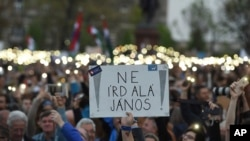 "Para pengunjuk rasa mengangkat poster yang bertuliskan ""Jangan Tanda Tangani, Janos"" merujuk pada Presiden Janos Ader seraya berunjuk rasa menentang perubahan undang-undang pendidikan tinggi yang dipandang banyak orang sebagai tindakan yang ditujukan untuk menutup Central European University, yang didirikan oleh milyader dan pengusaha Amerika kelahiran Hungaria, George Soros di depan gedung parlemen di Budapest, Hungaria, tanggal 9 April 2017 (foto: Zoltan Balogh/MTI via AP)"