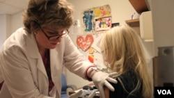 醫務人員星期五在波士頓塔夫茨醫學中心急診室為患者接種流感疫苗
