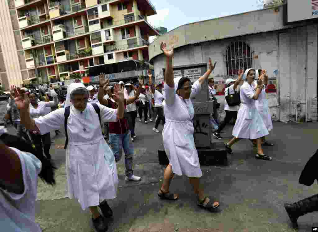 Nuns raise their arms during a women's march protesting repression against anti-government demonstrators in Caracas, Venezuela, Wednesday, Feb. 26, 2014. Former U.S. President Jimmy Carter is expressing concern about Venezuela's escalating political crisi