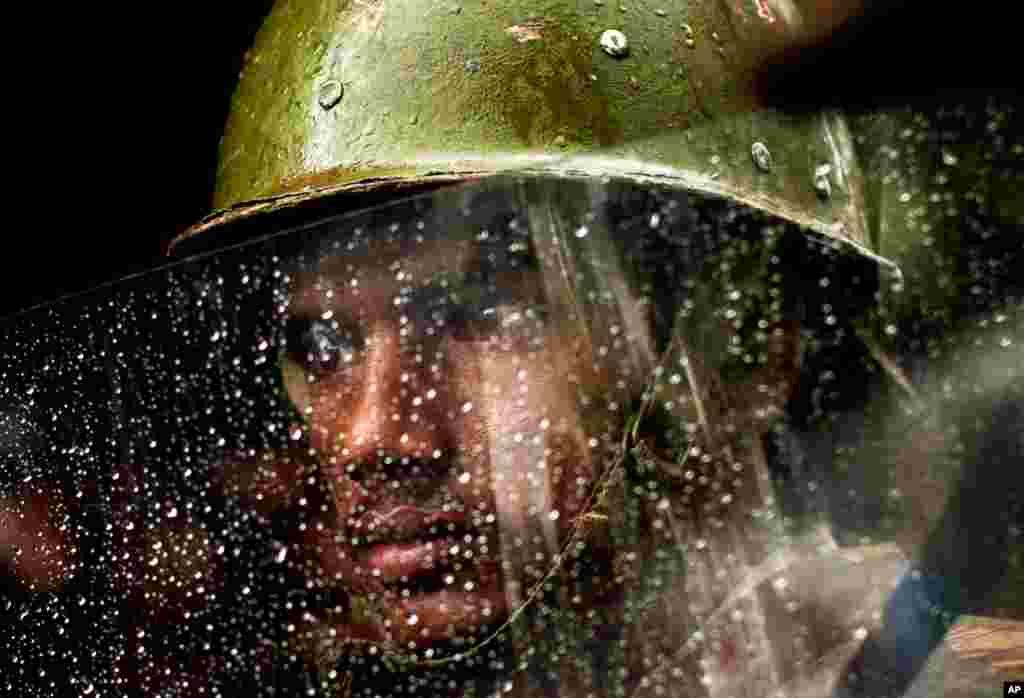 8月11日:印度首都新德里,一名警官在雨中从盾牌后面凝神观望。当时主要反对党印度人民党正在举行示威活动。(AP Photo/Kevin Frayer)