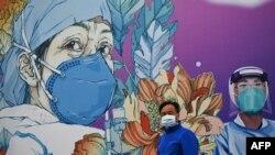 Čovjek sa maskom ispred murala na bolnici Lejšenšen koja je ponudila krevete za pacijente sa koronavirusom u Vuhanu, u provinciji Hubei, 11. aprila 2020.