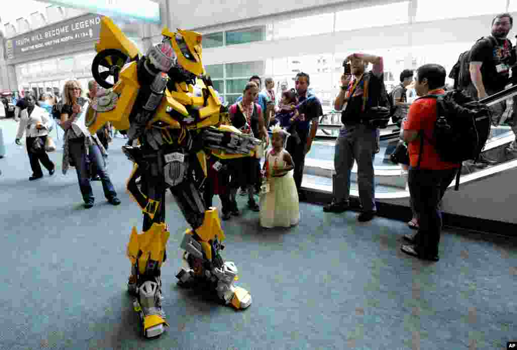 Lionel Lum, dressed as the Transformers' character Bumblebee, poses for photos on the third day of Comic-Con held at the San Diego Convention Center, July 14, 2012, in San Diego.