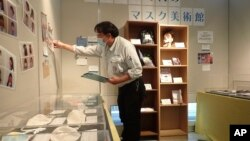 In this photo provided by curator Makoto Mochida of the Historical Museum of Urahoro, Mochida examines the newspaper clips and other items he is collecting to document how life was affected by the coronavirus pandemic at the museum in Urahoro, Hokkaido, n