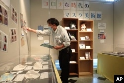 In this photo provided by curator Makoto Mochida of the Historical Museum of Urahoro, Mochida examines the newspaper clips and other items he is collecting to document how life was affected by the coronavirus pandemic at the museum.