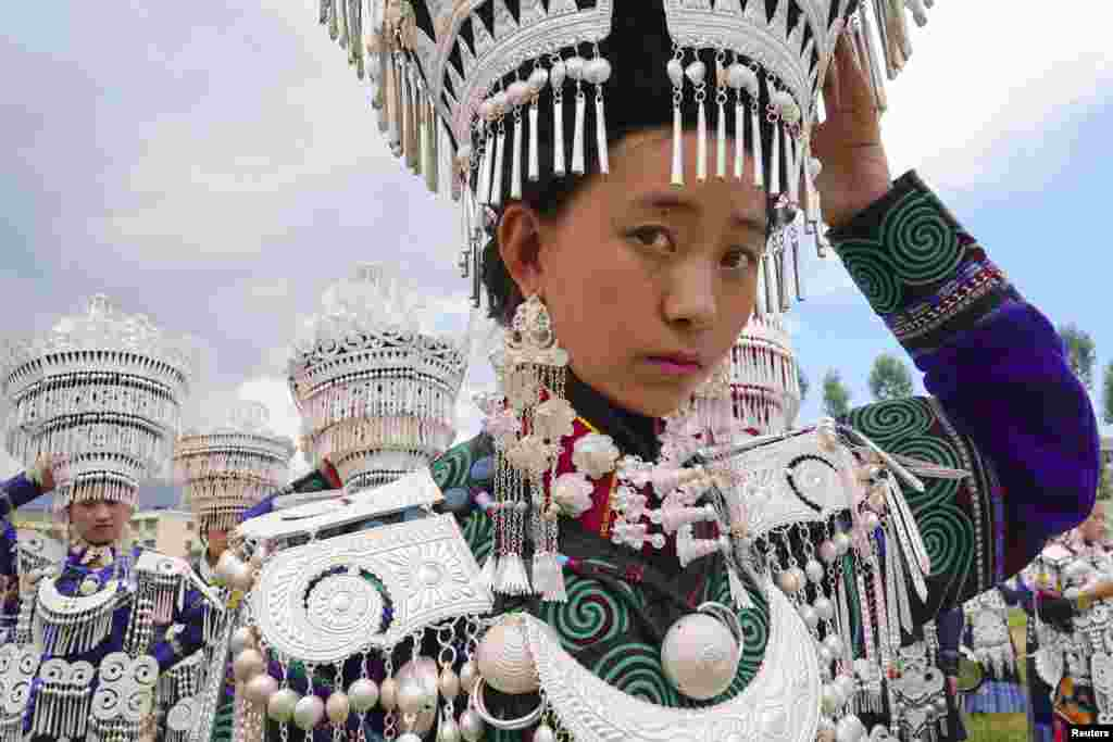 Yi ethnic minority girls wait to participate in a traditional performance to celebrate the Torch Festival in Butuo County, Sichuan province, China.
