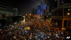 Tens of thousands of pro-democracy demonstrators, some waving lights from mobile phones, fill the streets in the main financial district of Hong Kong, Oct. 1, 2014.