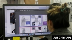 In this Feb. 15, 2018 photo, designer Tiffany Tam shows sketches of a handbag she designed on her computer at a Betabrand store in San Francisco.