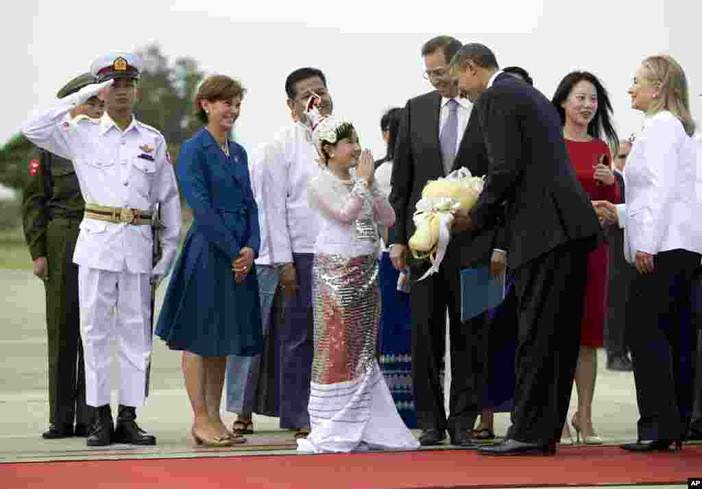 US President Barack Obama is presented with flowers as he and Secretary of State Hillary Rodham Clinton, right, arrive at Rangoon International Airport in Burma, Nov 19, 2012.