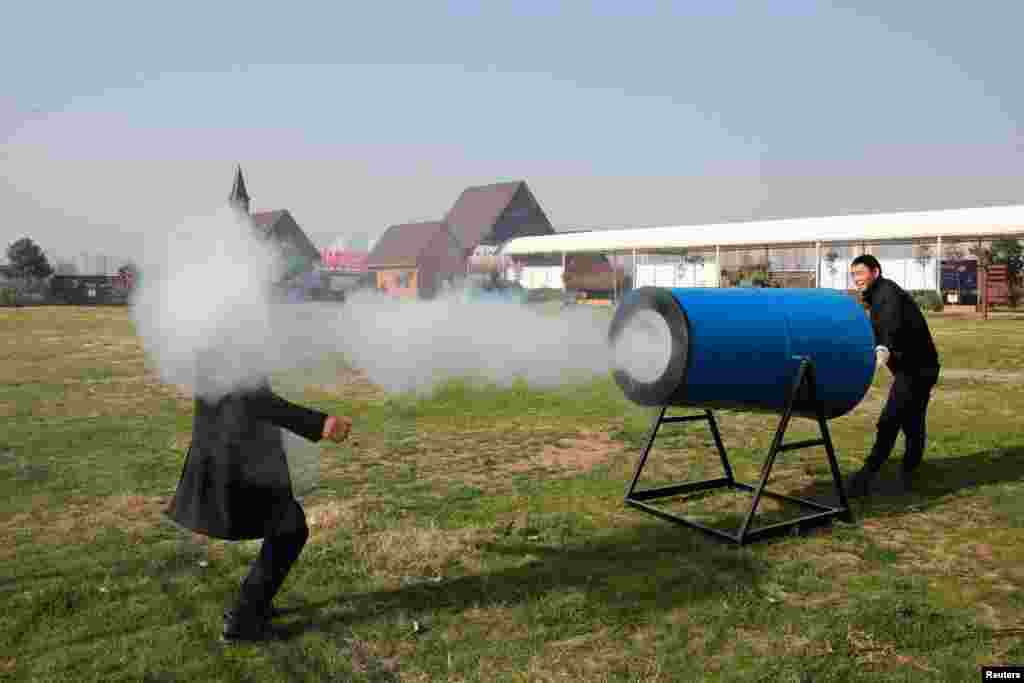 "People demonstrate a home-made ""smog cannon"" which fires cannonballs made of ""water and tobacco tar"" to remind people the importance of protecting environment, in Xiangyang, Hubei province, China."