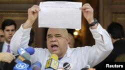 Jesus Torrealba, secretary of Venezuela's coalition of opposition parties (MUD), shows a copy of the form to collect signatures to begin the process of seeking a referendum to remove President Nicolas Maduro during a news conference in Caracas, Venezuela,