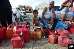 Ricardo Gonzalez sits on a gas container with his uncle Miguel Colon as hundreds of people wait in line since early morning hours to buy gasoline three days after the impact of Hurricane Maria in Carolina, Puerto Rico, Sept. 23, 2017.