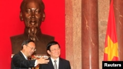 China's State Councillor Yang Jiechi, left, stands with Vietnam's President Truong Tan Sang in front of a bust of the late Vietnamese revolutionary leader Ho Chi Minh, at the Presidential Palace in Hanoi, Oct. 27, 2014.