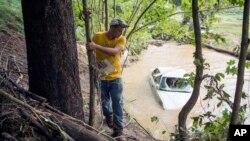 Ralph Whitaker observa un vehículo parcialmente sumergido mientras busca a su hermano, quien estaba desaparecido tras las mortales inundaciones en Flat Gap, Kentucky, el martes, 14 de julio de 2015.