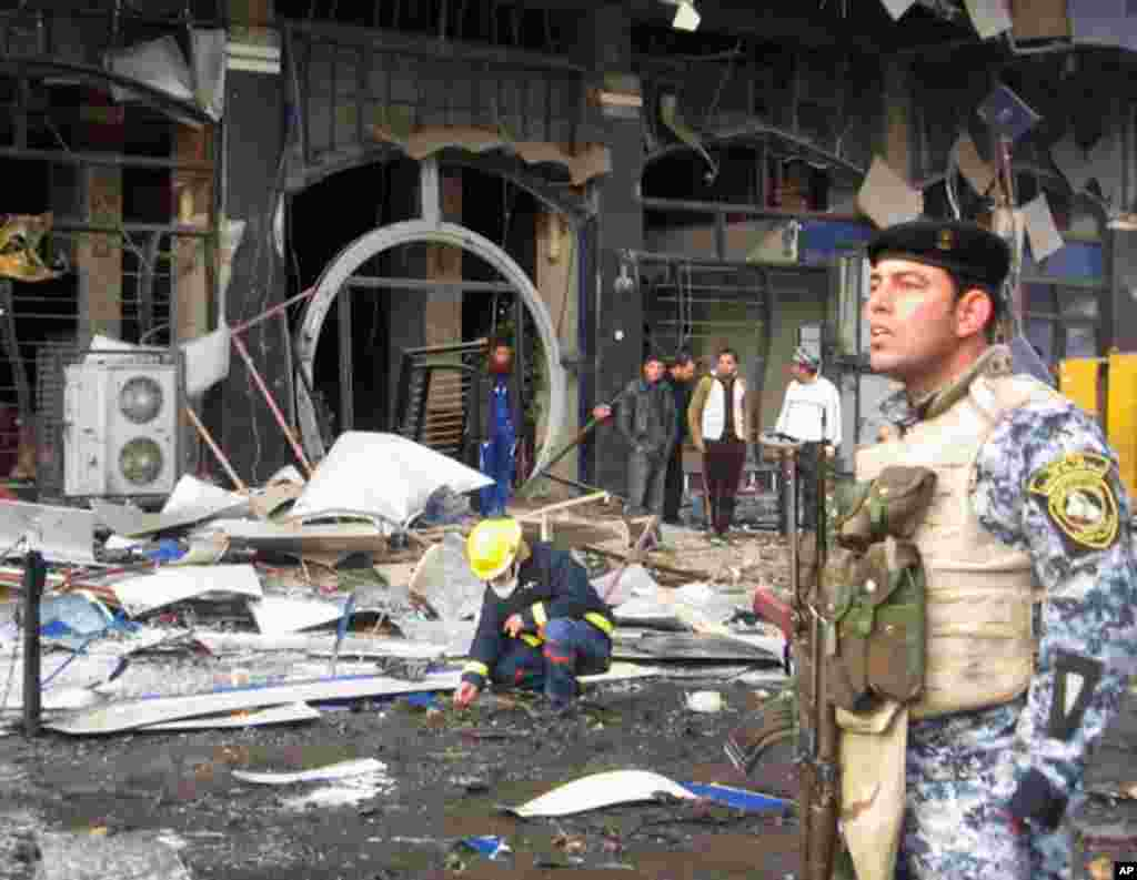 A police officer provides security at the site of a bomb attack in Baghdad's northwestern Kadhimiya district. (Reuters)