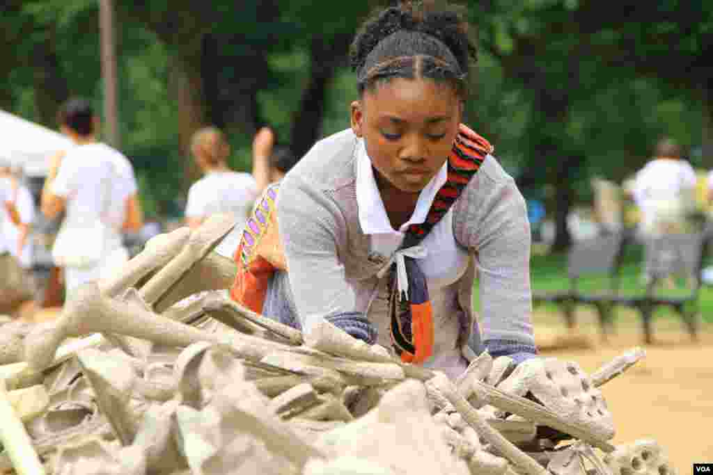 "Girl selects symbolic bones for display at the ""One Million Bones"" installation on the National Mall, Washington, D.C, June 8, 2013. (Jill Craig/VOA)"